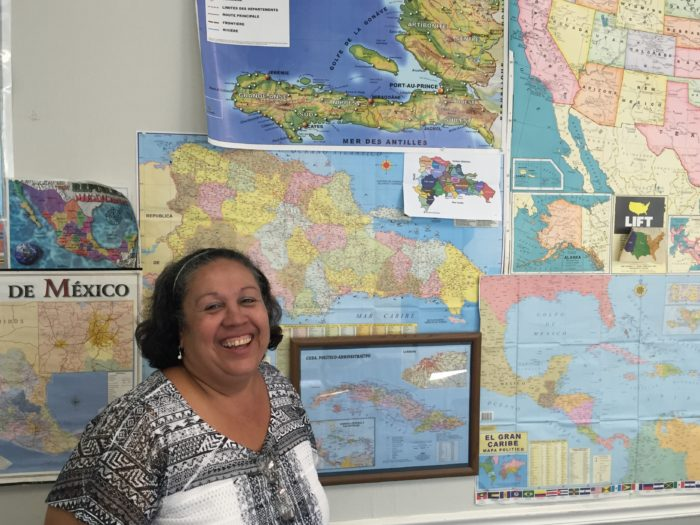 Leila Kurraro Bourse stands in front of maps that represent the home countries of her clients.